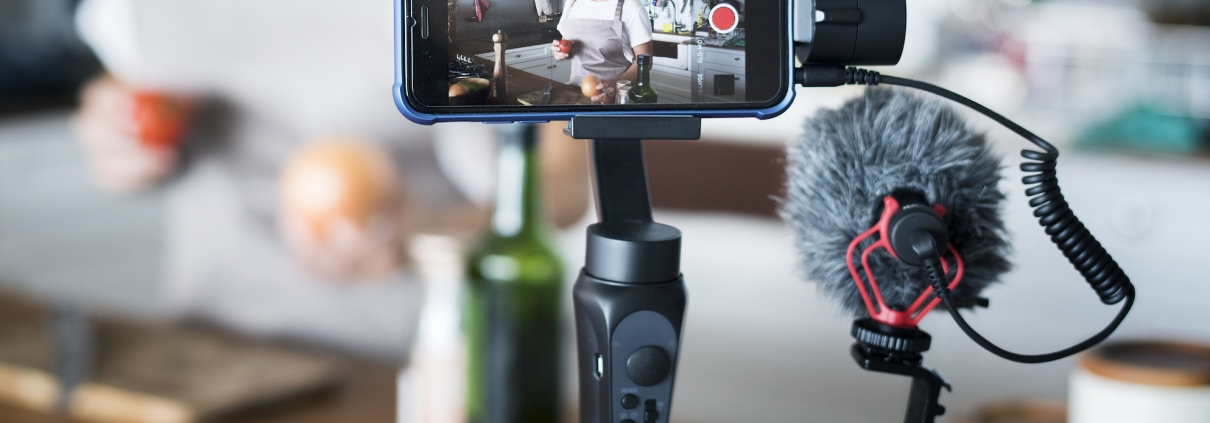 a phone a microphone set up to record a video in a kitchen
